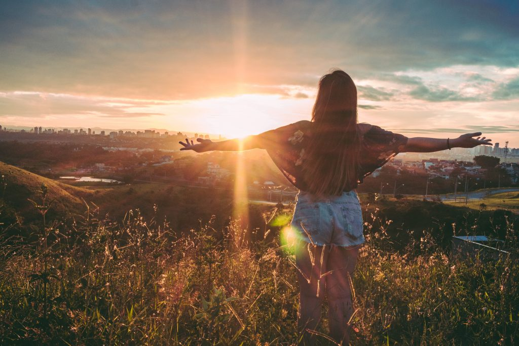 a girl spreading her hands towards the sunrise for the article 9 steps to financial freedom