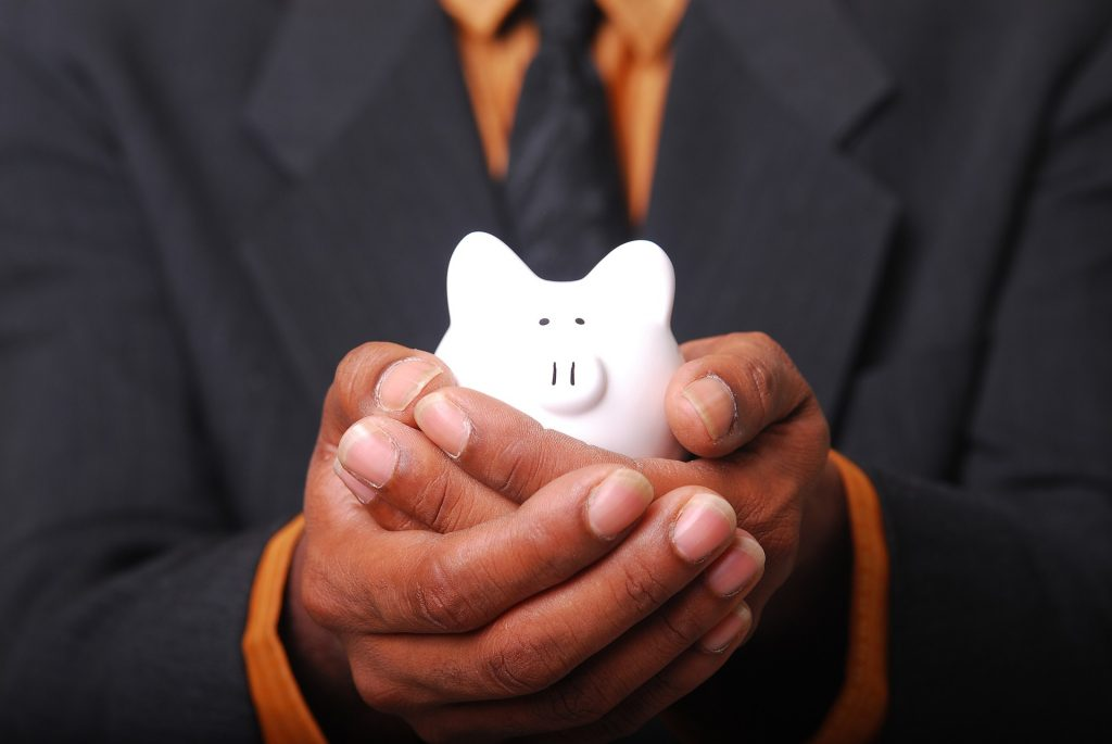 a man holding a small piggy bank