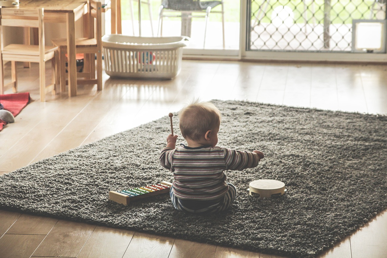 a picture of a baby playing with mucial intrument (Essential Baby Items article)