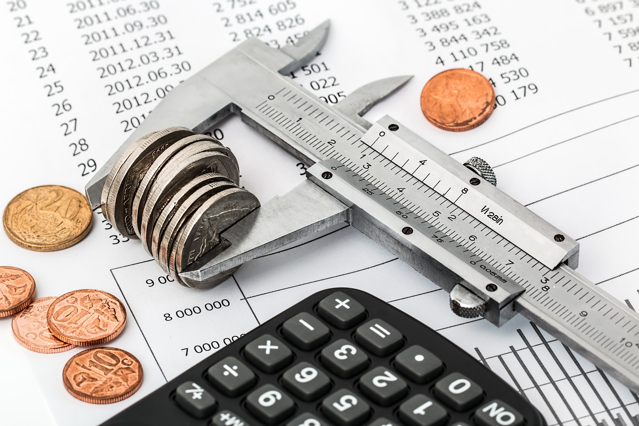 pictuere of a calcuator, coins, a ruler and a paper